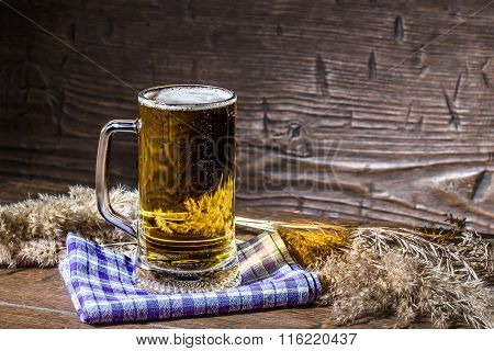 Mug Of Excellent Beer Is Standing On The Blue Napkin On Vintage Table Among Stalks