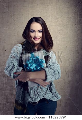 Portrait of attractive cheerful young woman holding gift box with blue bow over canvas background, toned and noise added