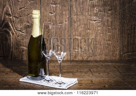 Bottle Of Champagne And Two Empty Wine Glasses Are Standing On A White Napkin On An Old  Table