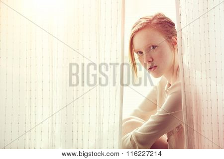 Face Of Beautiful Red Haired And  Freckles Young Girl Close-up House Near The Window.