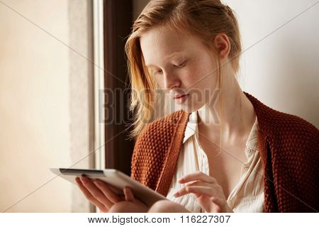 Tablet Computer. Relaxed Young Mixed Race Woman In Sofa Smiling Content, Happy And Reading On Tablet