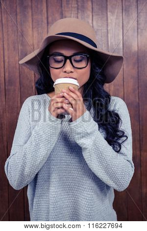 Asian woman drinking by disposable cup against wooden wall