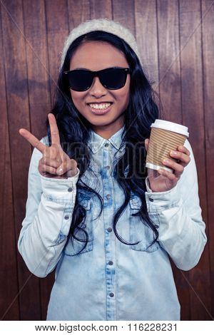Asian woman holding disposable cup against wooden wall