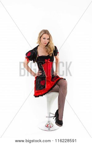 Young blond caucasian women in red dress is sitting on bar chair - Red Queen cosplay, white backgrou