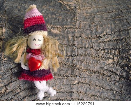 Small Children Puppet Figure, Holding Heart On Rough Wooden Bark Background With Copy Space.