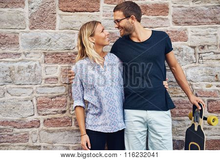Sweet Lovers Smiling Each Other Against Wall