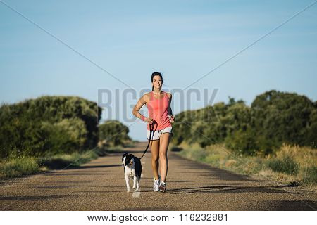 Woman And Dog Running On Country Road