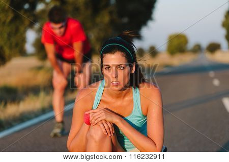 Tired Woman And Man Resting After Running Road Race