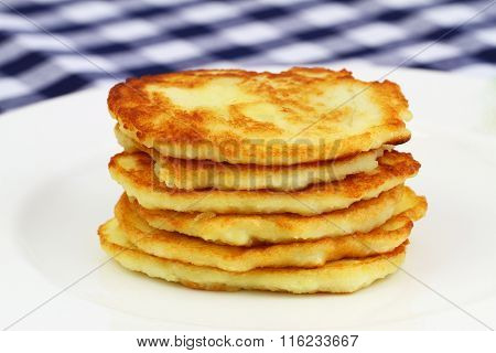 Potato fritters stacked up on white plate