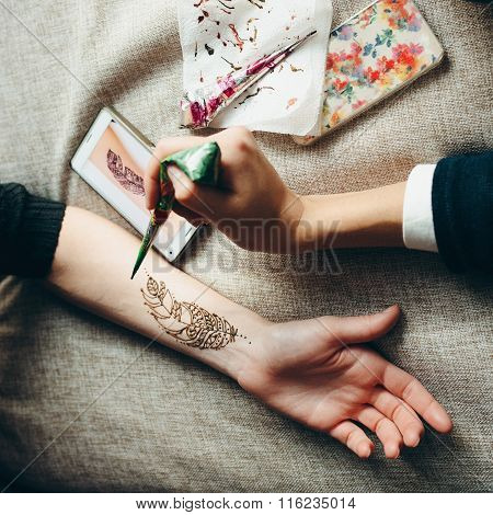 Picture hand being decorated with henna tattoo