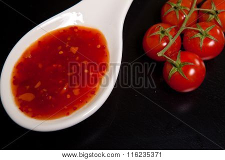 Spicy Tomato Sauce In A Gravy Boat Near Cherry Tomatoes On A Dark Background
