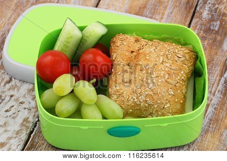 Healthy school lunch box containing whole grain roll with cheese and lettuce, grapes, cherry tomatoe