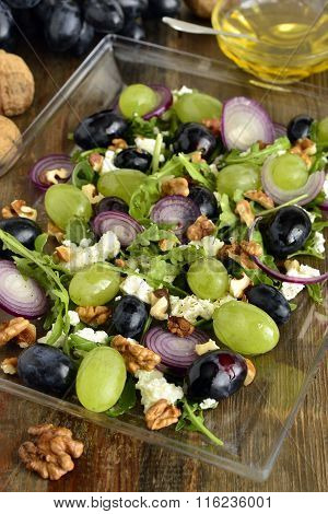 Salad with various grapes, goat cheese, purple onion, arugula and walnuts