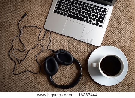 A laptop, headphones and coffee cup on a bed