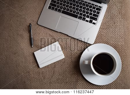 A laptop, coffee cup, notebook on a bed