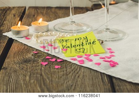 Sticky Note For Saint Valentine's Day And Tea Lights On Wooden Table