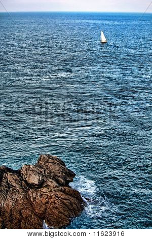 Lonely Sailboat Sailing At Sea Along Rocky Coastline