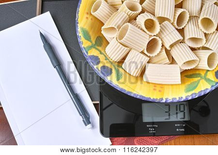 Weight control - kitchen scale with pasta, pencil and paper