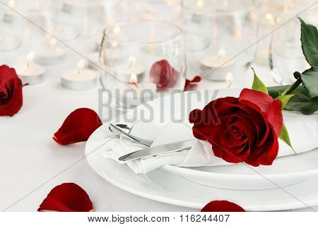 Romantic table setting with long stem red rose. Shallow depth of field with selective foc