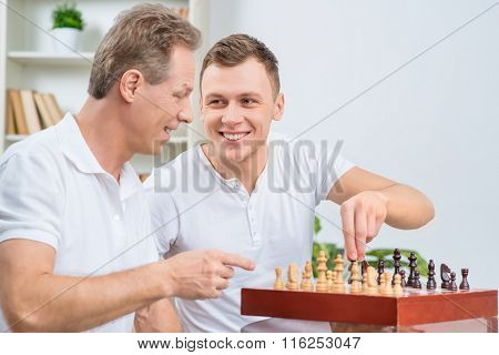 Father and his adult son playing chess