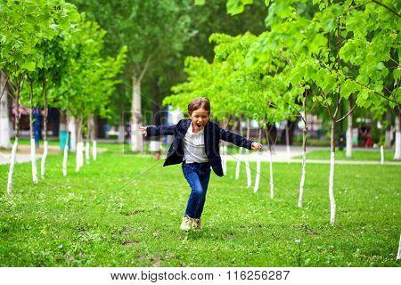 Happy little boy runs in a summer park