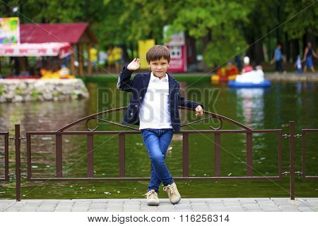Full length portrait of a little boy in the summer park