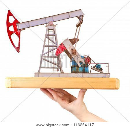 Oil Pump On A Wooden Board On A Female Hand