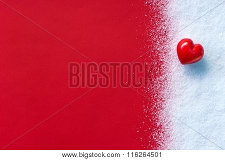 Red stone heart on white snow winter and red background