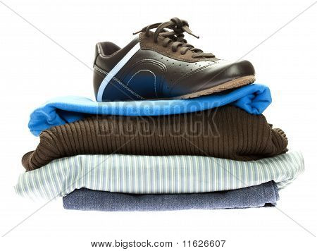 Shoes And A Mountain Of Clothes Isolated On White