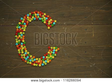 Letter C from alphabet made with star shape candy on a wooden background