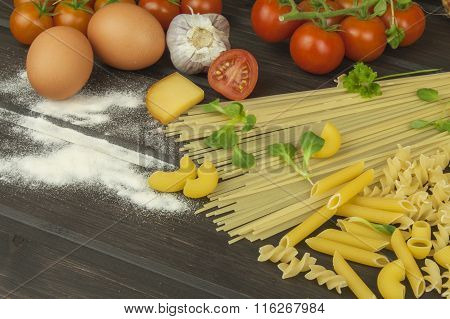 Spilled flour. Pasta and vegetables on a wooden table. Dietary food