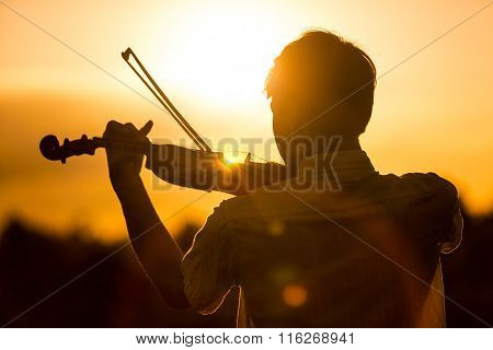 Young Man Or Boy Playing The Violin At Sunset