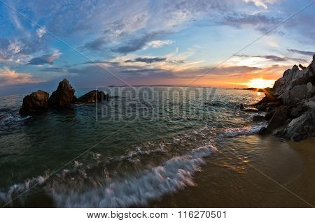 Sea rocks on a sandy beach at sunset in Sithonia, Chalkidiki
