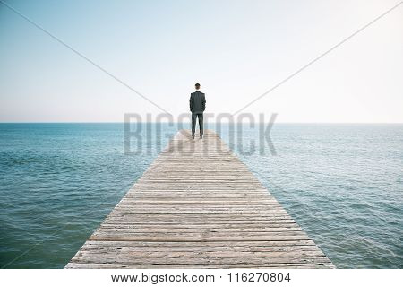 Man Standing On The Pier And Looking Into The Distance Of The Ocean