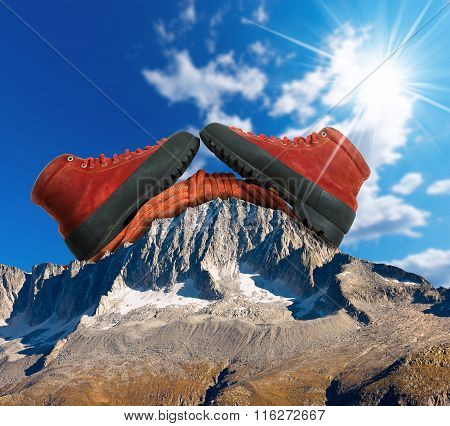 A pair of a mountaineering boots with a red climbing rope on a mountain peak with blue sky and sun rays. Mountain climbing concept