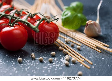 Pasta ingredients. Cherry-tomatoes spaghetti pasta fresh basil spices on a dark stone background