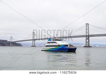 Suspension Oakland Bay Bridge And Tourist Boat In San Francisco, California, Usa