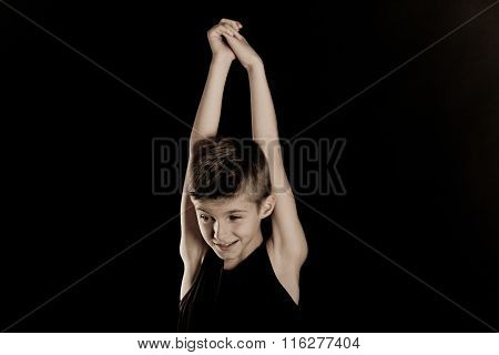 Slim Boy Raising His Arms Against Black Background
