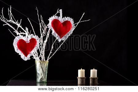 Pair of red hearts on a branch with two candles