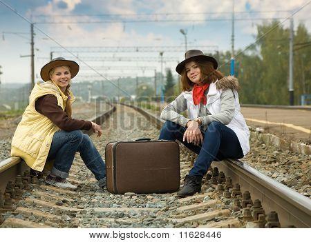 Pretty Girls Sitting On Rail