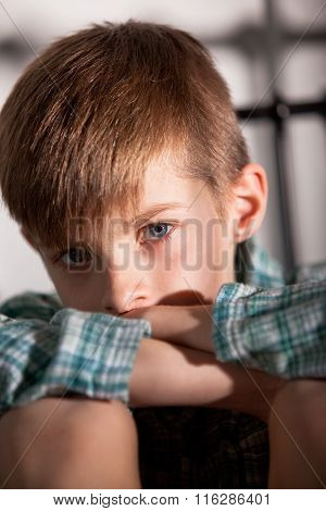 Sad Young Boy With Knees Up Looking At The Camera