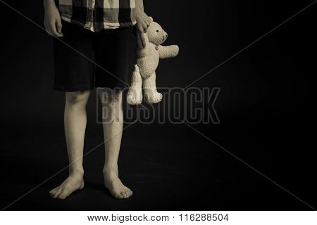Young Boy With Legs Scars Holding His Teddy Bear