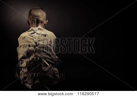 Lonely Poor Boy Facing Backward Against Black