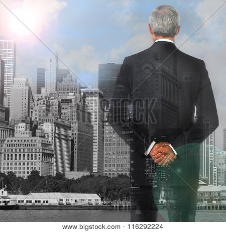 Businessman double exposure with his hands clasped behind his back with city background and lens flare.