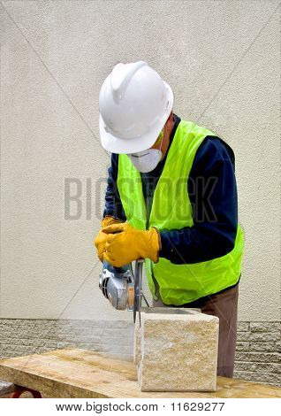 Construction worker in full safety gear cutting cement block with angle grinder
