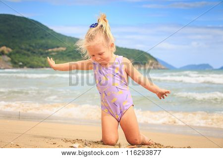 Side View Little Blond Girl Sits On Sand At Shell By Surf