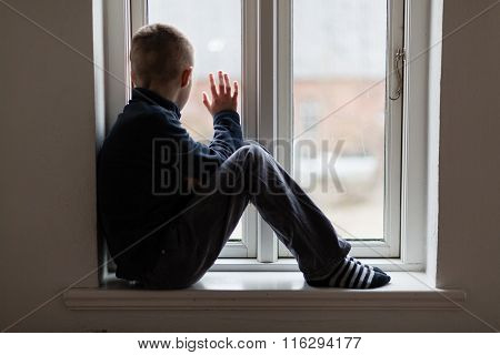 Young Boy Sitting On A Windowsill Waving