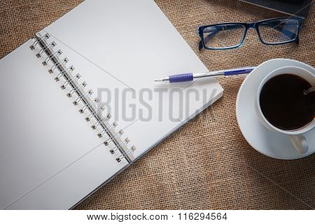 Still Life Of White Paper Page Of Note Book With Writing Pen On Table Top And Eye Glasses Hot Coffee