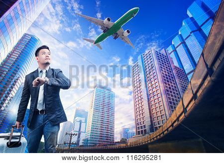 Young Business Man Standing Against Urban Building Scene Looking To Sky With Passenger Jet Plane Fly