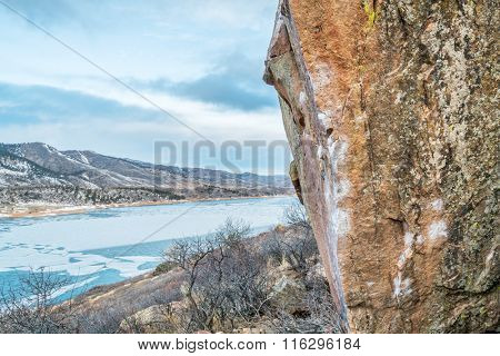 climbing wall with white chalk marks over Horsetooth Reservoir, Rotary Park, Fort Collins, Colorado, winter scenery with ice on a lake